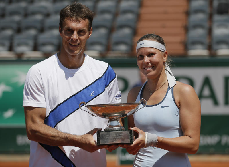 Lucie Hradecka, right, and Frantisek Cermak of the Czech Republic hold the trophy after winning the mixed doubles match 1-6, 6-4, 10-6, against Kristina Mladenovic of France and Daniel Nestor of Canada at the French Open tennis tournament, at Roland Garros stadium in Paris, Thursday June 6, 2013. (AP Photo/Petr David Josek)