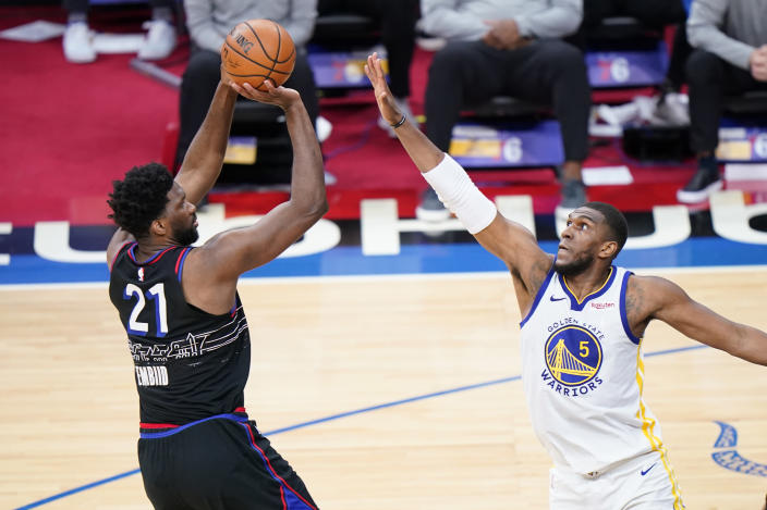 Philadelphia 76ers' Joel Embiid, left, goes up for a shot against Golden State Warriors' Kevon Looney during the second half of an NBA basketball game, Monday, April 19, 2021, in Philadelphia. (AP Photo/Matt Slocum)