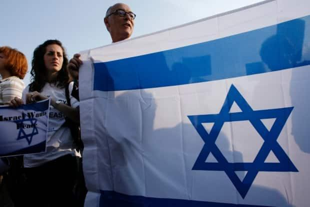 A man holds an Israeli flag during a demonstration in support of Israel in front of the United Nations European headquarters in Geneva, where the Durban conference on racism was held back in 2009. (Reuters - image credit)