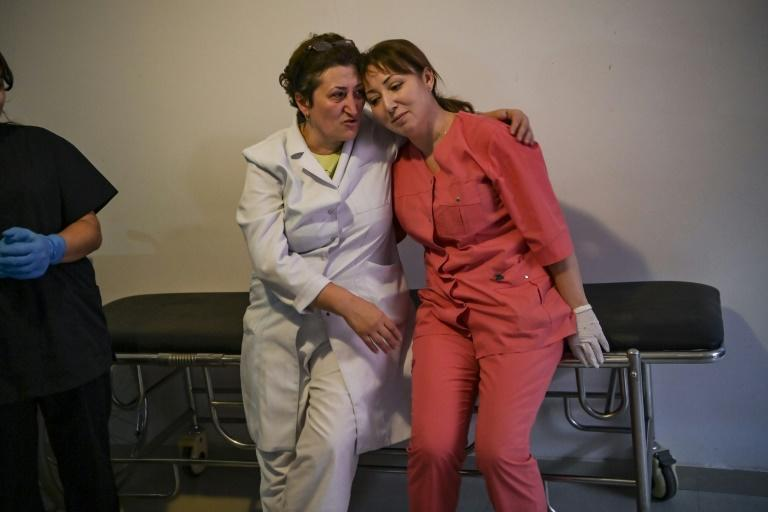 Paramedics comfort each others in the basement of a medical center outside the city of Stepanakert during the fighting between Armenia and Azerbaijan