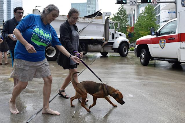 Evacuees Robin Alter, left, and her daughter Melissa Alter walk their dog, Dexter, into the George R. Brown Convention Center after Hurricane Harvey inundated the Texas Gulf Coast with rain, causing widespread flooding, in Houston, Aug. 27, 2017. Nick Oxford/Reuters