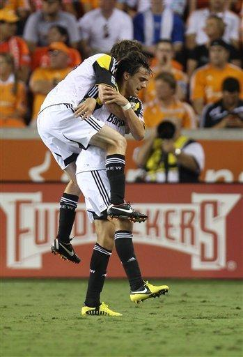 Columbus Crew's Eddie Gaven (12) jumps on his teammate Cole Grossman (22) after Grossman scored a goal during the first half of an MLS soccer game against the Houston Dynamo, Sunday, Aug. 19, 2012, in Houston. (AP Photo/Houston Chronicle, Karen Warren)