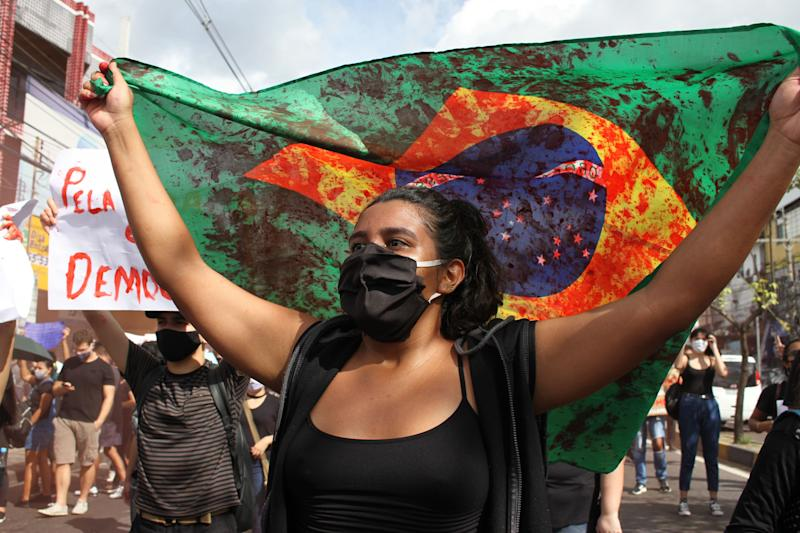 02 June 2020, Brazil, Manaus: A demonstrator holds a Brazilian flag during a protest. The demonstrators took to the streets in defence of democracy and criticised the anti-democratic course of Brazilian President Bolsonaro. Photo: Lucas Silva/dpa (Photo by Lucas Silva/picture alliance via Getty Images) (Photo: picture alliance via Getty Images)