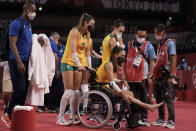 Brazil's Rosamaria Montibeller, #7, pushes in a wheelchair her teammate Macris Fernanda Silva Carneiro who was injured during a women's volleyball preliminary round pool A match against Japan, at the 2020 Summer Olympics, Thursday, July 29, 2021, in Tokyo, Japan. (AP Photo/Manu Fernandez)