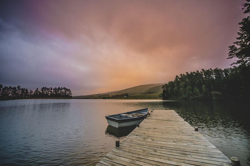 <p>A moored rowboat sits on the calm waters of the Cape Winelands Lakeland in South Africa.</p>