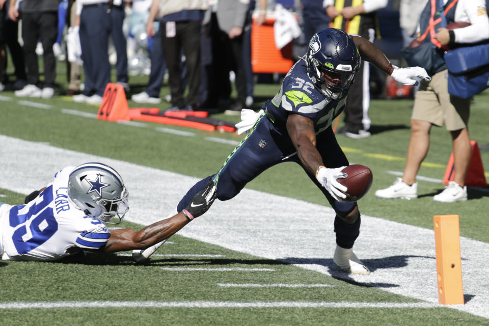 Seattle Seahawks running back Chris Carson (32) dives near the end zone as Dallas Cowboys cornerback Brandon Carr (39) attempts the tackle during the first half of an NFL football game, Sunday, Sept. 27, 2020, in Seattle. The Seahawks won 38-31. (AP Photo/John Froschauer)