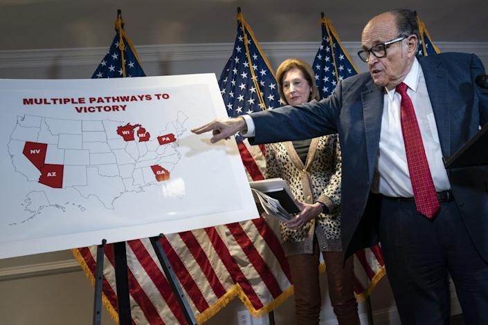 Rudy Giuliani points to a map as he speaks to the press about various lawsuits related to the 2020 election, inside the Republican National Committee headquarters on November 19, 2020 in Washington, DC. Also pictured, at center, is attorney Sidney Powell. (Photo by Drew Angerer/Getty Images)