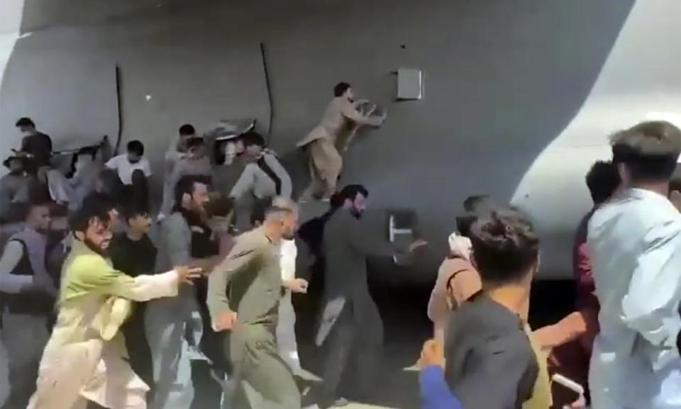 People climbing on to landing gear of US Airforce C17