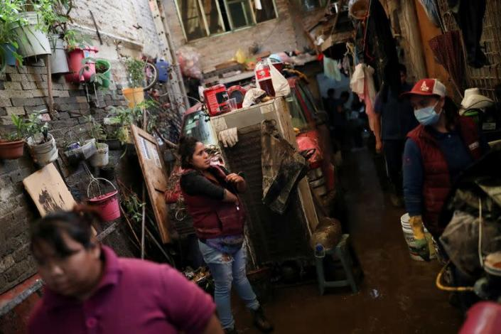 People clean up debris of the damage caused by heavy rainfall in the municipality of Ecatepec