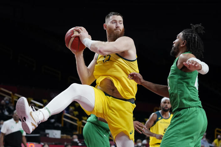 Australia's Aron Baynes grabs a rebound over Nigeria's Nnamdi Vincent, right, during a men's basketball preliminary round game at the 2020 Summer Olympics, Sunday, July 25, 2021, in Saitama, Japan. (AP Photo/Charlie Neibergall)