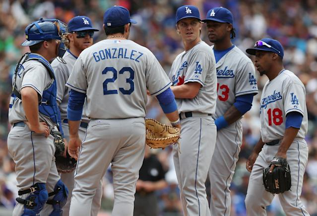 Los Angeles Dodgers starting pitcher Zack Greinke, third from right, confers with, from left, catcher Tim Federowicz, third baseman Justin Turner, first baseman Adrian Gonzalez, shortstop Hanley Ramirez and second baseman Chone Figgins after giving up an RBI-single to Colorado Rockies' Josh Rutledge in the fifth inning of a baseball game in Denver on Saturday, June 7, 2014. (AP Photo/David Zalubowski)