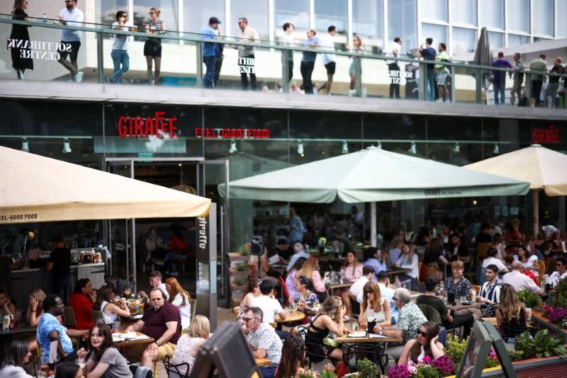 People sit at an outdoor restaurant on the South Bank during sunny weather, amid the coronavirus disease (COVID-19) outbreak, in London