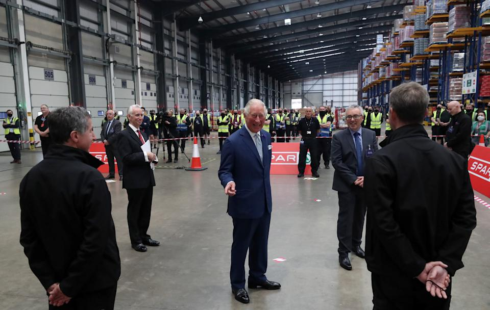 Britain's Prince Charles, Prince of Wales (C) reacts as he meets staff during a visit to Henderson Foodservice's food and grocery distribution centre in Newtownabbey, near Belfast, on September 30, 2020, where he thanked them for their efforts during the COVID-19 pandemic, and coping with the unprecedented demand they faced in recent months. (Photo by Niall Carson / POOL / AFP) (Photo by NIALL CARSON/POOL/AFP via Getty Images)