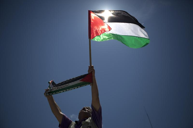 """A Palestinian protester raises up a flag and a banner reading """"Palestine"""" during a rally mon May 13, 2014 in Gaza city (AFP Photo/Mohammed Abed)"""