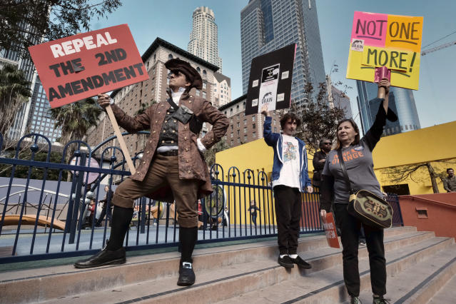 <p>Konstantine Anthony, left, joins other grassroots protestors during a rally against gun violence in downtown Los Angeles on Monday, Feb. 19, 2018. Hundreds of sign-carrying, chanting protesters have converged on a downtown Los Angeles park, demanding tougher background checks and other gun-safety measures following last week's deadly school shooting in Florida. (Photo: Richard Vogel/AP) </p>