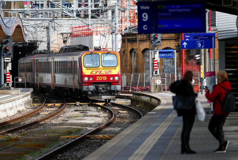 Passengers wait on a platform while a train arrives at Luxembourg railway station