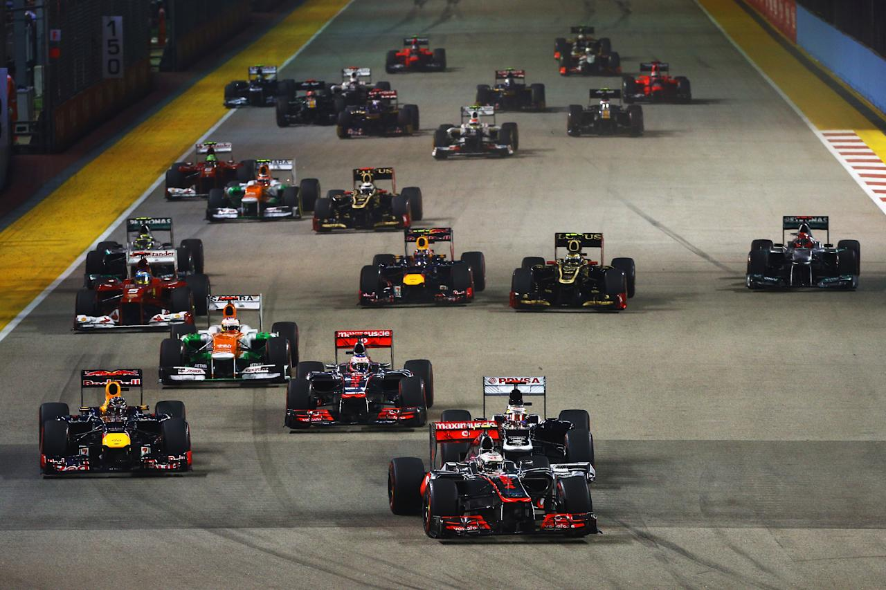 SINGAPORE - SEPTEMBER 23:  Lewis Hamilton of Great Britain and McLaren leads the field into the first corner at the start of the Singapore Formula One Grand Prix at the Marina Bay Street Circuit on September 23, 2012 in Singapore, Singapore.  (Photo by Paul Gilham/Getty Images)
