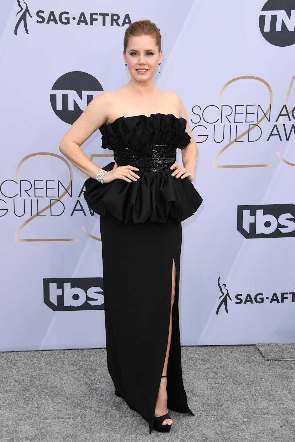 <p>Wearing a black ruffled gown with a slit by Celine by Heidi Slimane with Cartier jewels and Jimmy Choo heels.</p>