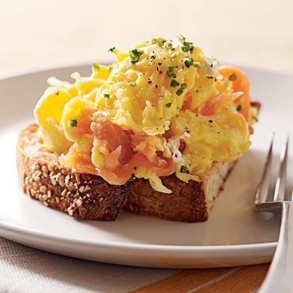 """<p>Folding Nova Scotia salmon and <a href=""""https://www.myrecipes.com/ingredients/cream-cheese-recipes"""" rel=""""nofollow noopener"""" target=""""_blank"""" data-ylk=""""slk:cream cheese"""" class=""""link rapid-noclick-resp"""">cream cheese</a> into freshly scrambled eggs and serving on toast makes this dish a filling, satisfying way to start your day. Cut the cream cheese while chilled, and let stand at room temperature about 15 minutes before using.</p>"""