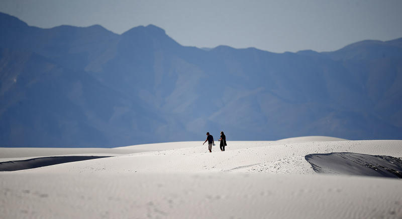 In this Thursday, March 5, 2020, photograph, a couple walks over gypsum dunes in White Sands National Park at Holloman Air Force Base, N.M. With the new coronavirus changing how people navigate their lives, folks have looked to the great outdoors for exercise and entertainment in these turbulent times. The new coronavirus causes mild or moderate symptoms for most people, but for some, especially older adults and people with existing health problems, it can cause more severe illness or death. (AP Photo/David Zalubowski)