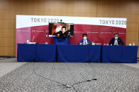 Olympic Games Executive Director of IOC Christophe Dubi (on screen) waves as chief of main operation centre of Tokyo 2020 Hidemasa Nakamura, center, and The Tokyo Organizing Committee of the Olympic and Paralympic Games spokespersons and Masa Takaya, right, are seen at the end of an online press briefing for the presentation of the version three of Tokyo 2020 Playbook in Tokyo, Tuesday, June 15, 2021. (Behrouz Mehri/Pool Photo via AP)