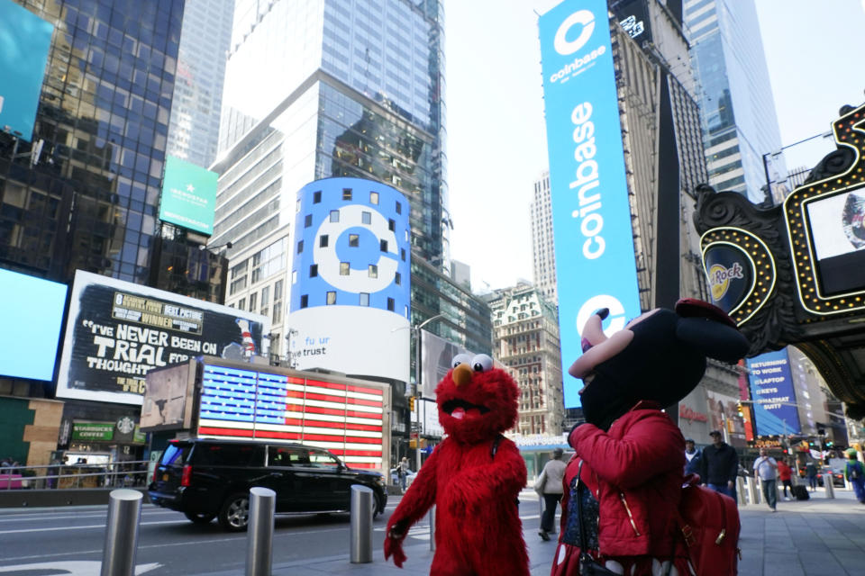 Costumed characters pass the Nasdaq MarketSite during the Coinbase IPO, in New York's Times Square, Wednesday, April 14, 2021. Wall Street will be focused on Coinbase Wednesday with the digital currency exchange becoming a publicly traded company. (AP Photo/Richard Drew)