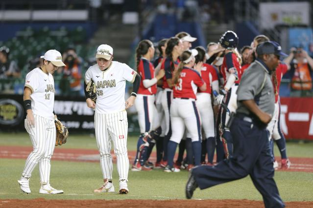 Japan's players, in white jersey, react as U.S. team members, in red jersey, celebrate after Women's Softball World Championship game Saturday Aug. 11, 2018 in Makuhari, east of Tokyo. United States to a 4-3 win over Japan and into the final of the women's world softball championship. (Kyodo News via AP)