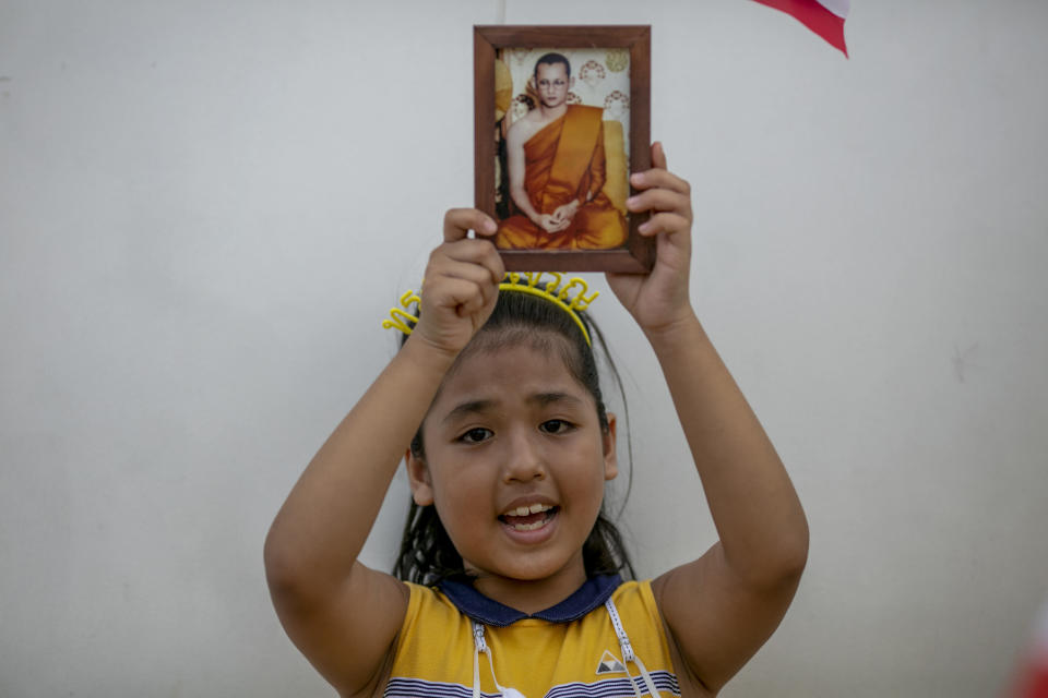 A child displays an image of late King Bhumibol Adulyadej as she gathers with adults in front of the Grand Place in Bangkok, Thailand, Sunday, Nov. 1, 2020. Hundreds of royalists gathered close to the Grand Palace in which King Maha Vajiralongkorn is scheduled to visit for a Buddhist religious ceremony. (AP Photo/Wason Wanichakorn)