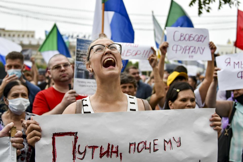 """A woman shouts holding a poster reads """"Putin, why do you hate Russians?"""" during a rally supporting Khabarovsk region's governor Sergei Furgal in Khabarovsk, 6,100 kilometers (3,800 miles) east of Moscow, Russia, Saturday, Aug. 1, 2020. Thousands of demonstrators rallied Saturday in the Russian Far East city of Khabarovsk to protest the arrest of the regional governor, continuing a three-week wave of opposition that has challenged the Kremlin. (AP Photo/Igor Volkov)"""