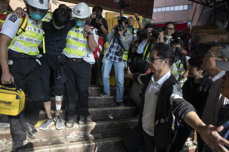 President of the Polytechnic University Jin-Guang Teng, second from right, looks as an injured protester is helped by medics to leave the campus in Hong Kong on Wednesday, Nov. 20, 2019. A small group of protesters refused to leave Hong Kong Polytechnic University, the remnants of hundreds who took over the campus for several days. They won't leave because they would face arrest. Police have set up a cordon around the area to prevent anyone from escaping. (AP Photo/Ng Han Guan)