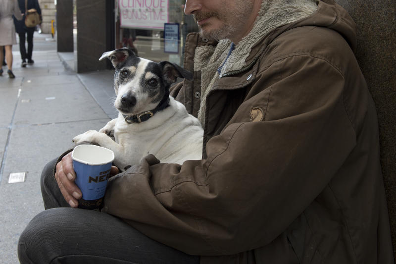 A homeless man holds his dog while begging in central London.