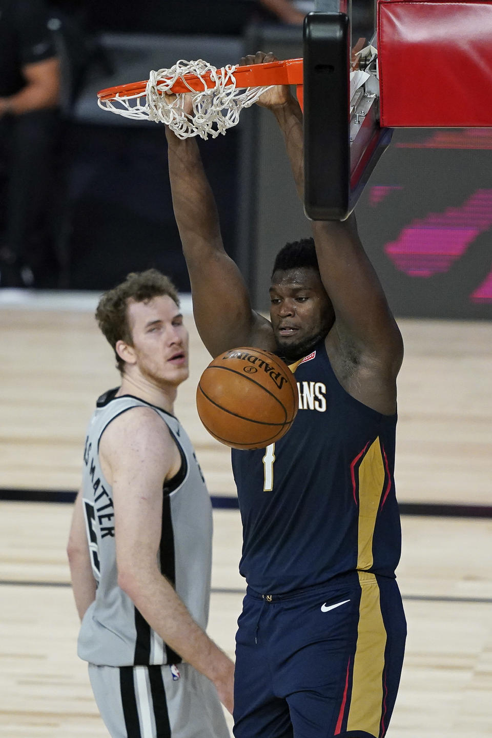 New Orleans Pelicans forward Zion Williamson, right, dunks the ball in front of San Antonio Spurs center Jakob Poeltl during the second half of an NBA basketball game, Sunday, Aug. 9, 2020, in Lake Buena Vista, Fla. (AP Photo/Ashley Landis, Pool)