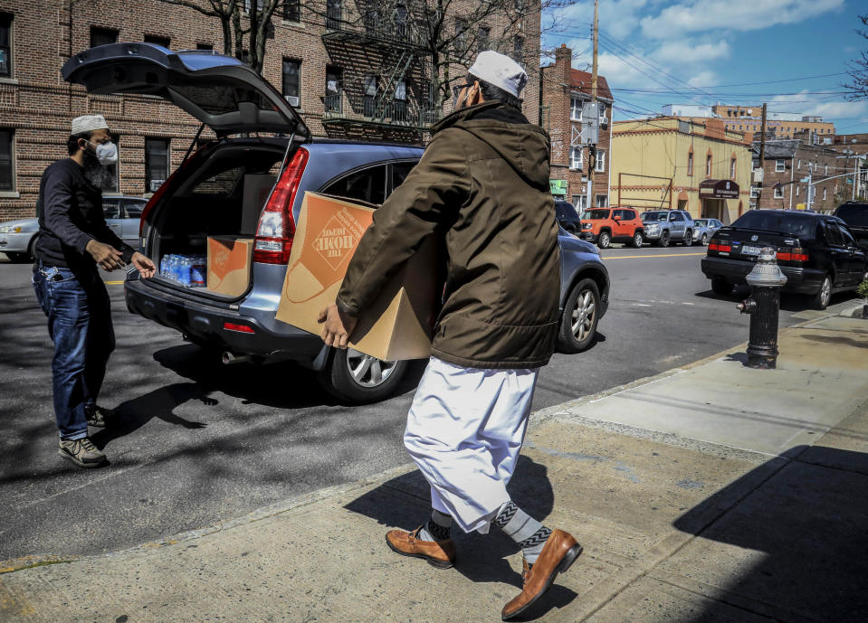 """In this Wednesday, April 22, 2020, photo, Elmhurst Hospital in the Queens borough of New York, the city's deadliest hospital for patients stricken with COVID-19, can be seen nearby as Imam Mufti Mohammed Ismail, right, and volunteer Mohammad Q Ullah, left, prepare to deliver food supplies to those impacted by coronavirus restrictions. """"I'm receiving so many phone calls from families who are saying, 'we are not poor, but the situation has [made] it so hard, so we need a food box,'"""" said Ismail, who leads An-Noor Cultural Center and masjid for a mostly Bangladeshi Muslim community. (AP Photo/Bebeto Matthews)"""