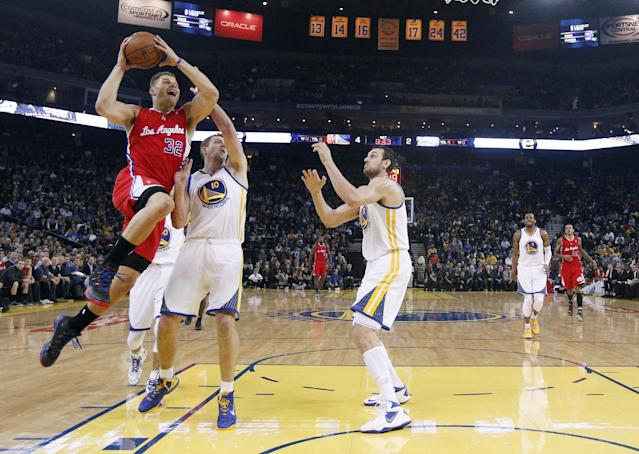 Los Angeles Clippers' Blake Griffin, left, goes up for a shot next to Golden State Warriors' David Lee (10) and Andrew Bogut, center, during the first half of an NBA basketball game on Thursday, Jan. 30, 2014, in Oakland, Calif. (AP Photo)