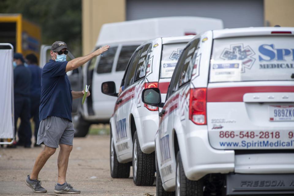 A man directs emergency vehicles as they arrive to evacuate people at a mass shelter Thursday, Sept. 2, 2021 in Independence, La. Multiple nursing home residents died after Hurricane Ida, but full details of their deaths are unknown because state health inspectors said Thursday that they were turned away from examining conditions at the facility to which they had been evacuated. (Chris Granger/The Times-Picayune/The New Orleans Advocate via AP)