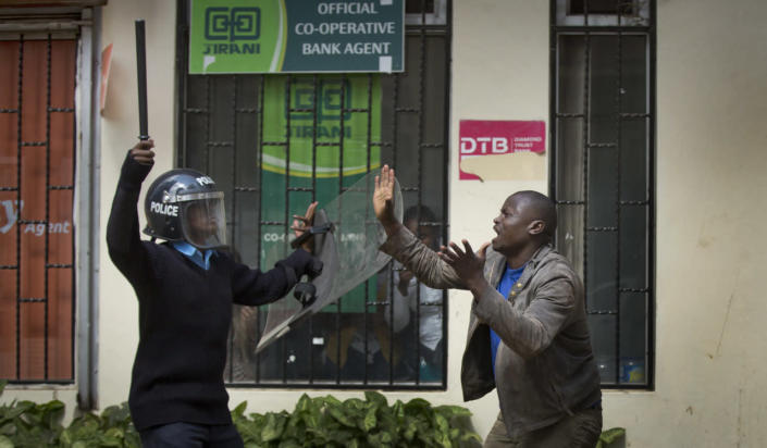 An opposition supporter pleads with a riot policeman after being beaten with a wooden club by one, managing to escape, but then being cornered by another, during a protest in downtown Nairobi, Kenya, May 16, 2016. Kenyan police have tear-gassed and beaten opposition supporters during a protest demanding the disbandment of the electoral authority over alleged bias and corruption. (AP Photo/Ben Curtis)