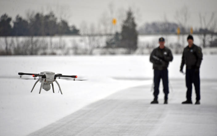 FILE – In this Jan. 15, 2015, file photo, Michigan State Police Sgt. Matt Rogers and Trooper Don Zinz bring an Aeryon SkyRanger drone in for a landing during a demonstration of the agency's new Unmanned Aircraft System at the Michigan State Police training track in Dimondale, Mich. More than a year after the U.S. Interior Department grounded hundreds of Chinese-made drones it was using to track wildfires and monitor dams and wildlife, the future of drone use by the federal government remains unmapped. The latest complication: Legislation moving through Congress that would block the U.S. government from using drones made in China. (Dale G. Young/Detroit News via AP)