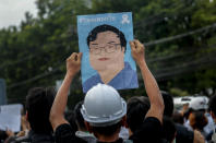 A pro-democracy activist displays a poster featuring an image of recently detained protest leader Parit Chiwarak during a demonstration at Kaset intersection, suburbs of Bangkok, Thailand, Monday, Oct. 19, 2020. Thailand's embattled Prime Minister Prayuth Chan-ocha said Monday that there were no plans to extend a state of emergency outside the capital, even as student-led protests calling for him to leave office spread around the country. (AP Photo/Sakchai Lalit)