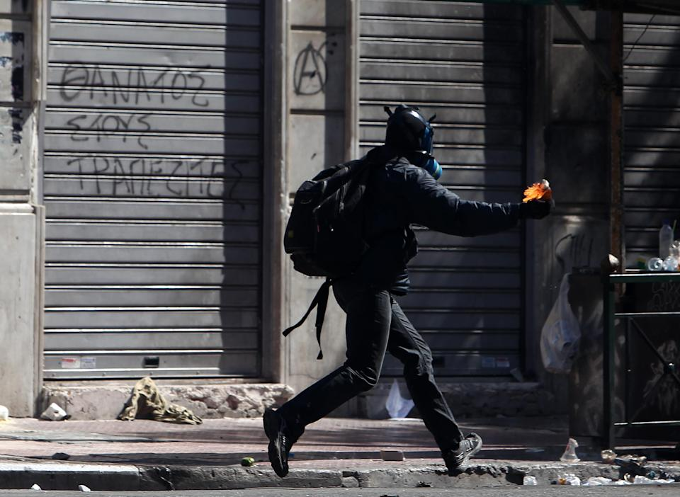 A protester prepares to throw a petrol bomb at riot police during a nationwide general strike in Athens, Wednesday, Sept. 26, 2012. Police clashed with protesters hurling petrol bombs and bottles in central Athens Wednesday after an anti-government rally called as part of a general strike in Greece turned violent. About 50,000 people joined the union-organized march in central Athens on Wednesday, held during a general strike against new austerity measures planned in the crisis-hit country. (AP Photo/Thanassis Stavrakis)