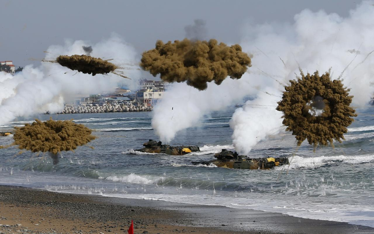 Amphibious assault vehicles of the South Korean Marine Corps throw smoke bombs as they move to land on shore during a U.S.-South Korea joint landing operation drill in Pohang March 31, 2014. The drill is part of the two countries' annual military training called Foal Eagle, which began on February 24 and runs until April 18. North Korea declared a no-sail warning on Monday for areas off its west coast near a disputed border with South Korea and has notified the South that it will conduct firing drills, a South Korean government official said. The warning comes amid heightened tensions surrounding the North after the U.N. Security Council condemned Pyongyang for its mid-range missile launches last week, just as the leaders of South Korea, Japan and the United States met to discuss the North's arms programme. REUTERS/Kim Hong-Ji (SOUTH KOREA - Tags: POLITICS MILITARY TPX IMAGES OF THE DAY)