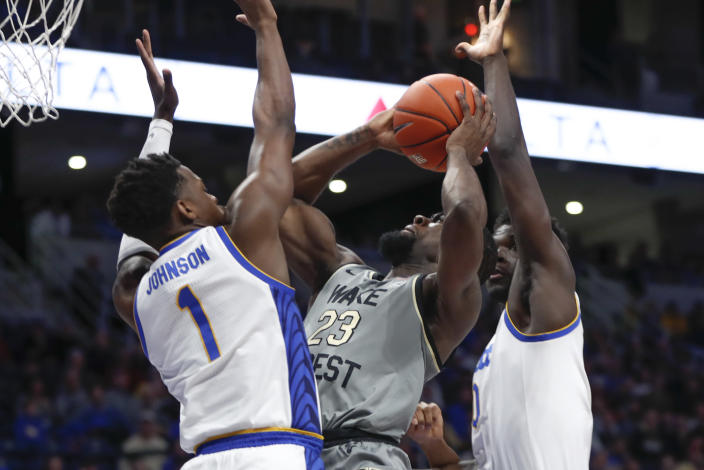 Wake Forest's Chaundee Brown (23) shoots between Pittsburgh's Xavier Johnson (1) and Eric Hamilton (0) during the first half of an NCAA college basketball game, Saturday, Jan. 4, 2020, in Pittsburgh. (AP Photo/Keith Srakocic)