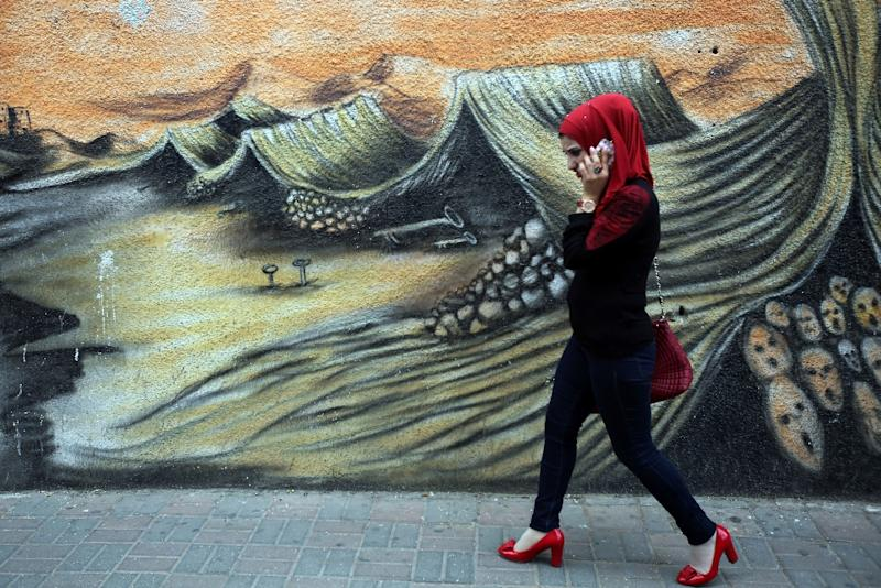 "A Palestinian woman walks past graffiti on May 13, 2015 in the West Bank city of Ramallah illustrating the ""Nakba"" or ""catastrophe"" in Arabic, in reference to the birth of the state of Israel 67-years-ago in then British-mandate Palestine (AFP Photo/Abbas Momani)"