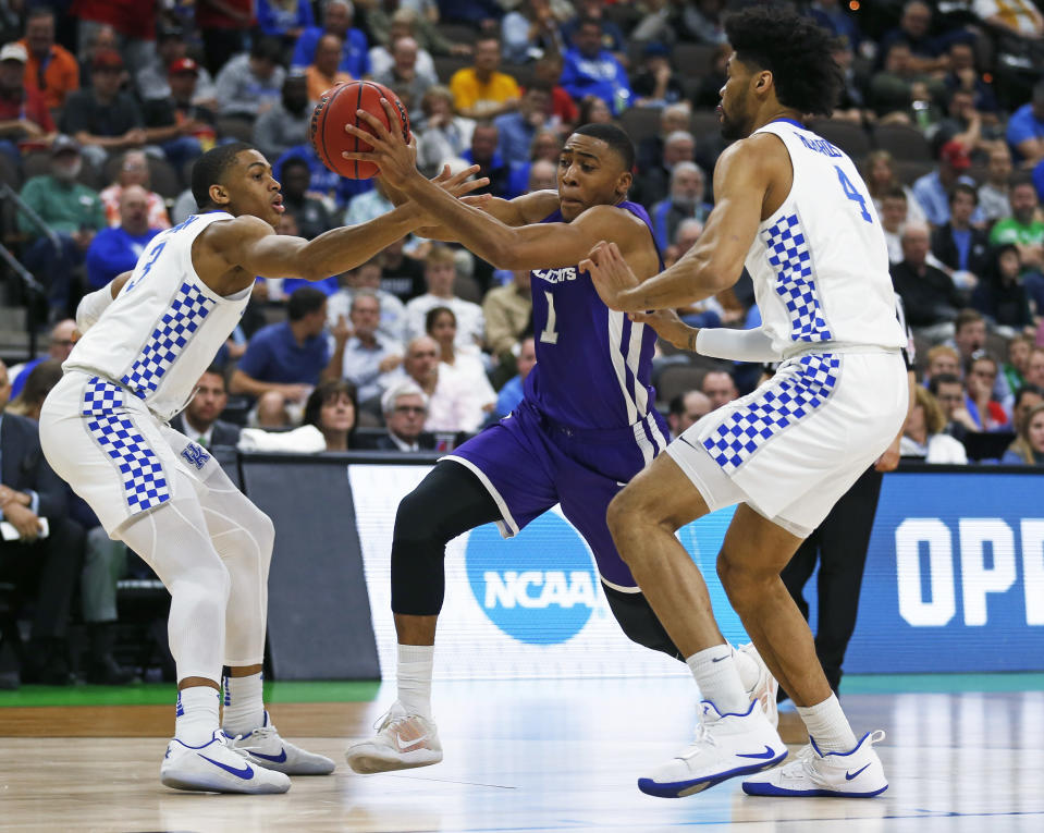 Abilene Christian's Jaren Lewis (1) moves between Kentucky's Keldon Johnson, left, and Nick Richards (4) during the first half of a first-round game in the NCAA mens college basketball tournament in Jacksonville, Fla., Thursday, March 21, 2019. (AP Photo/Stephen B. Morton)