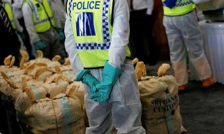 Police officers stand next to the haul of seized cocaine sacks to be destroyed under judicial supervision in Katunayake, Sri Lanka January 15, 2018. REUTERS/Dinuka Liyanawatte