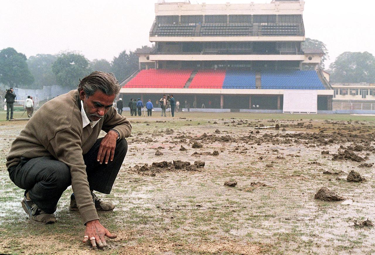 An Indian grounds inspector checks the pock-marked cricket pitch at the Ferozeshah Kotla Stadium in New Delhi 07 January after Hindu militants of the Shiv Sena Party dug up the Test match cricket pitch ahead of a planned Pakistani cricket tour of India later this month.  Officials said the pitch, though damaged, would be able to accommodate the tourists for their first Test in New Delhi 28 January.  AFP PHOTO