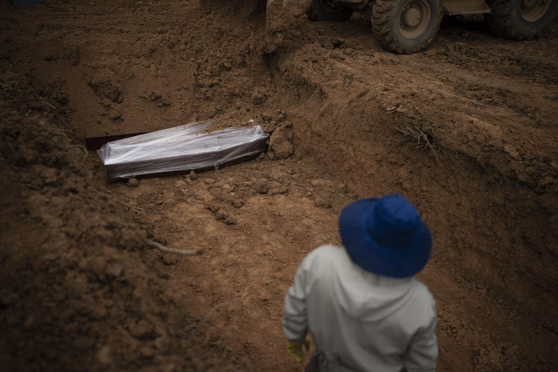 A cemetery worker stands in a common grave as a bulldozer dumps soil over coffins at the Nossa Senhora Aparecida cemetery, amid the new coronavirus pandemic in Manaus, Brazil, Wednesday, May 13, 2020. The new section of the cemetery was opened last month to cope with a surge in deaths. (AP Photo/Felipe Dana)