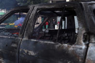 A family look at a burning car after heavy clashes in the coastal town of Khaldeh, south of Beirut, Lebanon, Sunday, Aug. 1, 2021. At least two people were killed on Sunday south of the Lebanese capital when gunmen opened fire at the funeral of a Hezbollah commander who was killed a day earlier, an official from the group said. (AP Photo/Bilal Hussein)