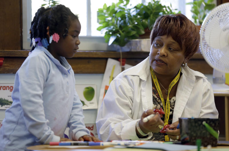 In this photo taken Wednesday, Nov. 13, 2013, Elmira Warren talks with Camil Douthit, 5, a student in Warren's pre-school class at Clay Elementary Community Education school in St. Louis. Warren is a participant in a pilot program called Home Works that sends public school teachers into their students' homes several times annually with the hope the home visits will boost both student academic achievement as well as parental involvement. (AP Photo/Jeff Roberson)