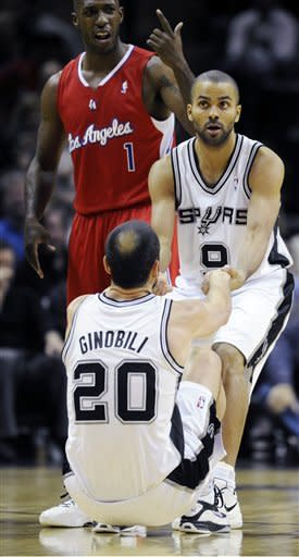 San Antonio Spurs guard Tony Parker, of France, helps up Manu Ginobili, of Argentina, (20) after Ginobili was fouled by Los Angeles Clippers guard Chauncey Billups on a 3-point shot attempt during the first half of an NBA basketball game in San Antonio, Wednesday, Dec. 28, 2011. The Spurs won 115-90. (AP Photo/Bahram Mark Sobhani)