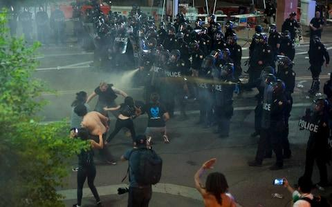 Police use tear gas to break up protesters gathered outside of the Phoenix - Credit: AFP